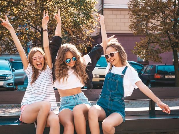 トレンディな夏服の3人の若い美しい笑顔流行に敏感な女の子の肖像画。通りのベンチに座っているセクシーな屈託のない女性。サングラスで楽しんでいるポジティブなモデル。 無料写真