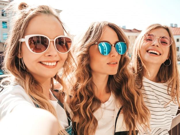 夏服で3人の若い笑顔ヒップスター女性。スマートフォンでセルフポートレート写真を撮る女の子。通りでポーズをとるモデル。肯定的な顔の感情を示す女性 無料写真