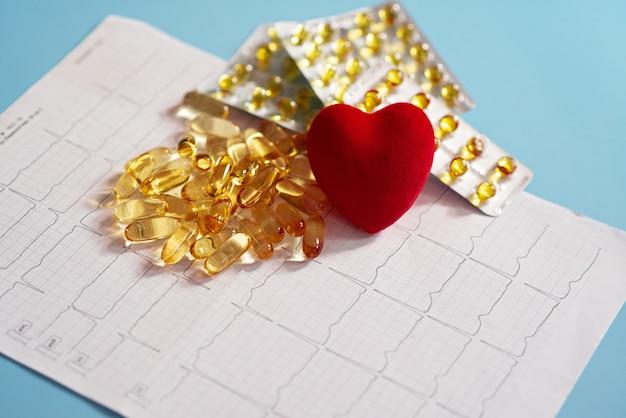 Омега-3 капсулы на кардиограмме рядом с красным сердцем Premium Фотографии