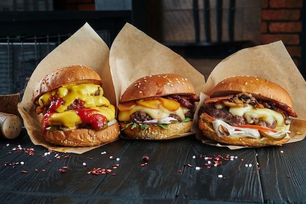 3 вкусных бургера с разными начинками на деревянном черном столе. бургер с ананасами, грибами и сыром чеддер. набор гамбургеров аппетитный Premium Фотографии