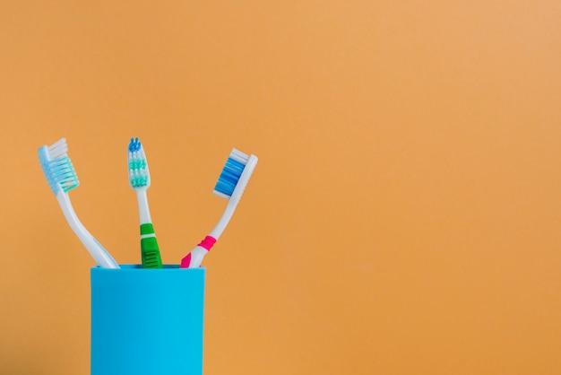 オレンジ色の背景を保持する3つの異なる歯ブラシ 無料写真