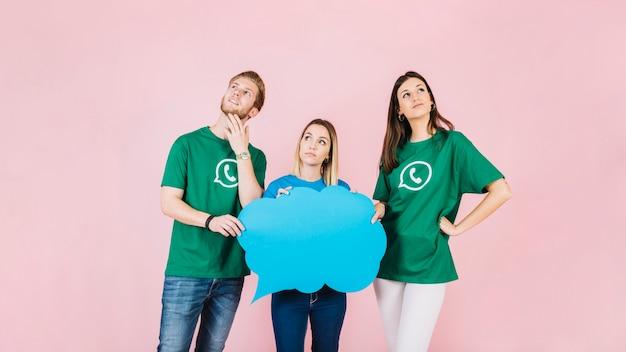 青いスピーチバブルを抱く3人の若い友人 無料写真