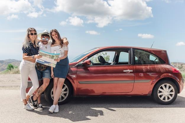 道路上の現代的な車の近くに地図立っている3人の友人 無料写真