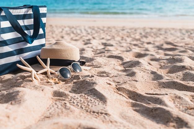 砂の上に大きな袋を持つ3つのスターフィッシュ 無料写真