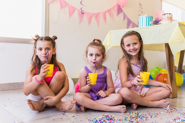 家で誕生日パーティーを祝っている間ジュースを飲む3人の少女 無料写真