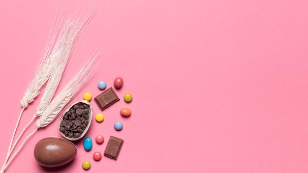 チョコレートのイースターエッグとピンクの背景の宝石キャンディーと3つの小麦の穂 無料写真
