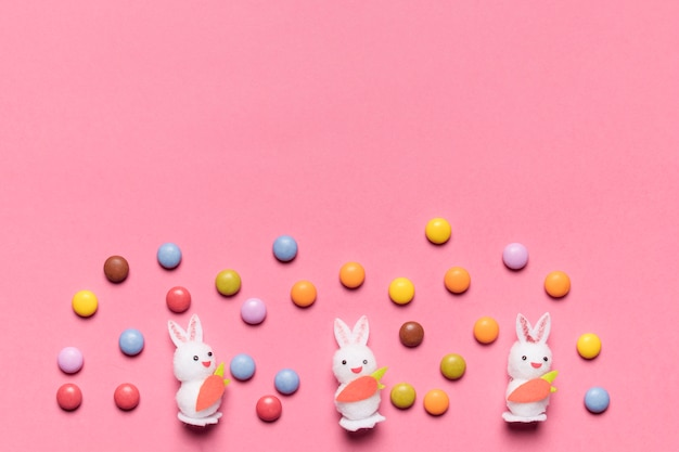 ピンクの背景にカラフルな宝石キャンディーと3つの白いウサギ 無料写真
