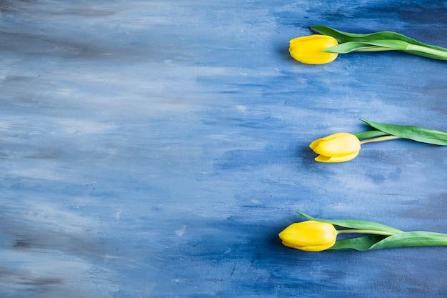 青いテーブルの上の3つのチューリップの花 無料写真