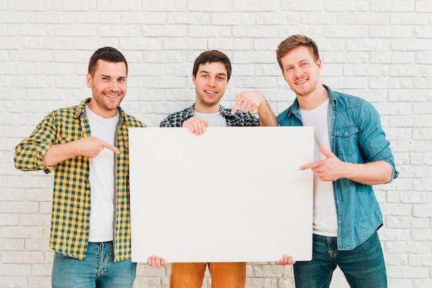 白い空白のプラカードを示す3人の男性の友人の肖像画 無料写真