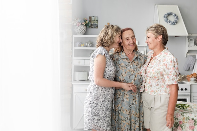 3人の女性が一緒に立っていると自宅で笑顔 無料写真