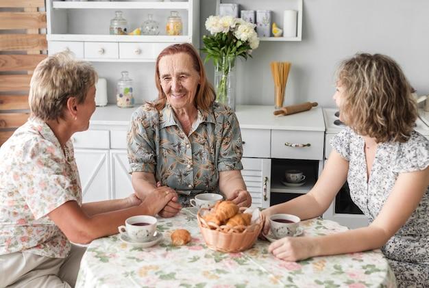 コーヒーブレーク中に何かを話している3世代の女性 無料写真
