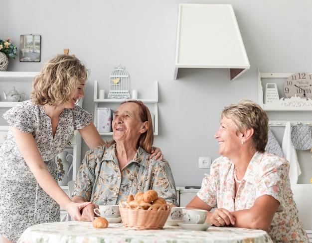 台所で朝食をとった女性の3世代 無料写真