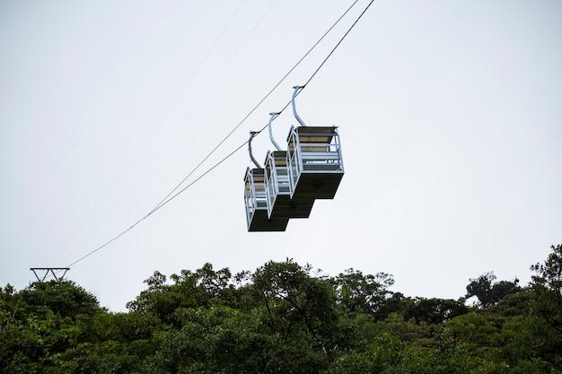 コスタリカの熱帯雨林の上の3つの空のケーブルカー 無料写真
