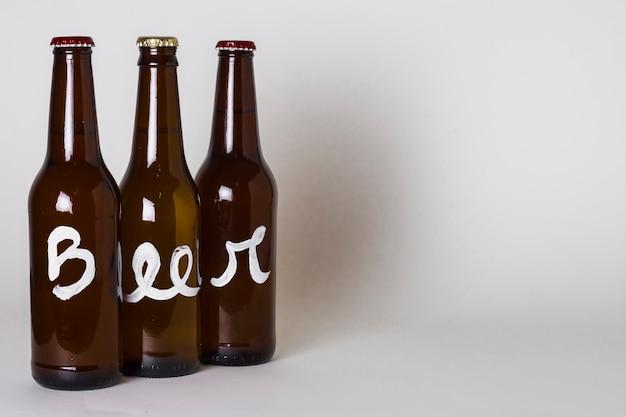 テーブルの上のビールの3つのボトルの側面図 無料写真