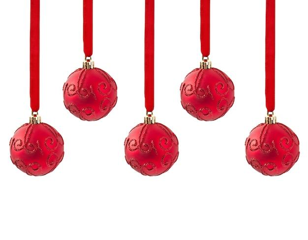 白で隔離されるリボンに掛かっている3つの赤いクリスマスボール 無料写真