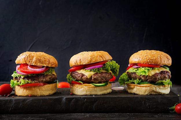 牛肉のハンバーガーと暗い背景に新鮮な野菜の3つのハンバーガー。 Premium写真