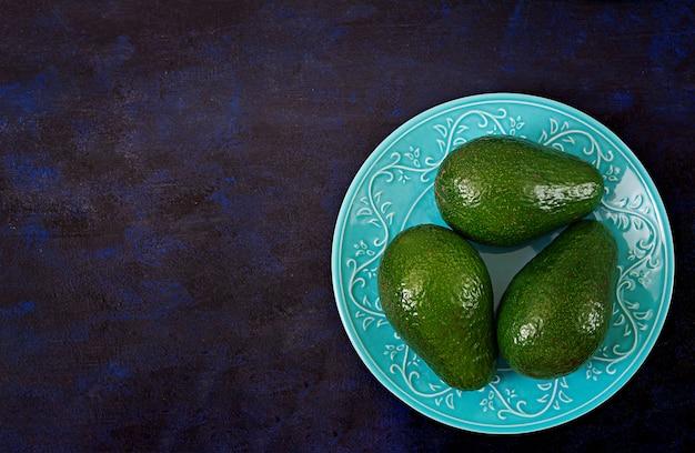 暗いテーブルの上の3つの熟したアボカド。健康食品のコンセプト。上面図 無料写真