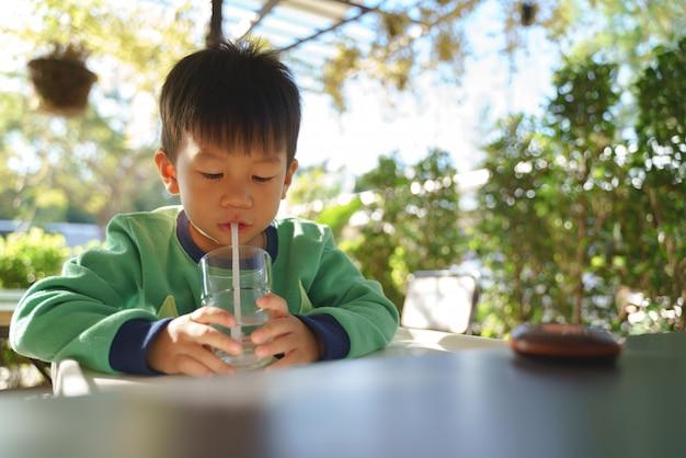 3-х летний азиатский ребенок питьевой воды Premium Фотографии