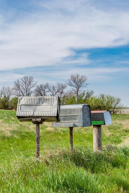 カナダのサスカチュワン州農村部の大草原の上の3つの古い金属農家のメールボックスの行 Premium写真