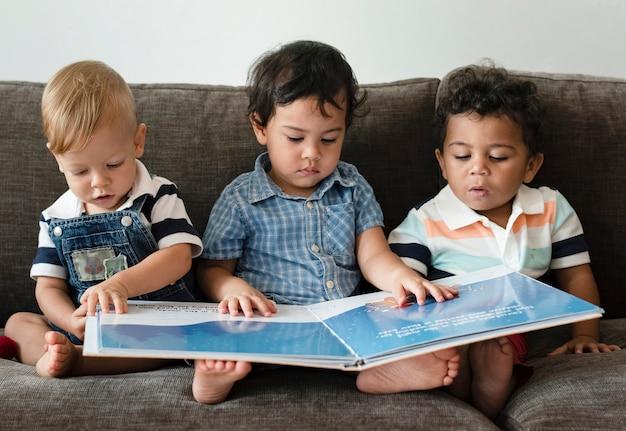 ソファで本を読んで3人の男の子 Premium写真