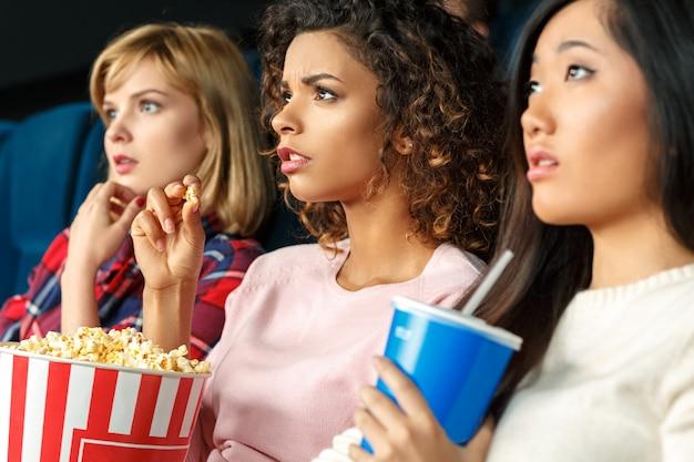映画の魔法!映画館に注意深く座って映画を見ている3人の美しい女性の友人のクローズアップショット Premium写真