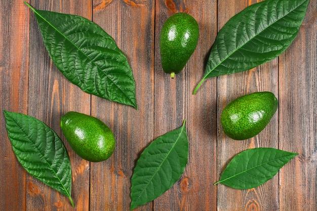 葉を持つ3つの緑の生熟したアボカドは、茶色の木製のテーブルの上にあります。平置き。上面図。 Premium写真