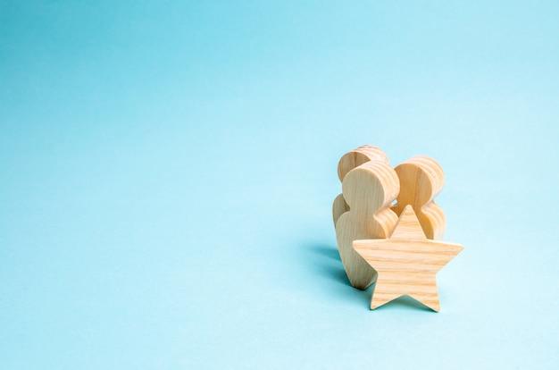 人と星の3つの木像。違いのサイン、前向きな評価 Premium写真
