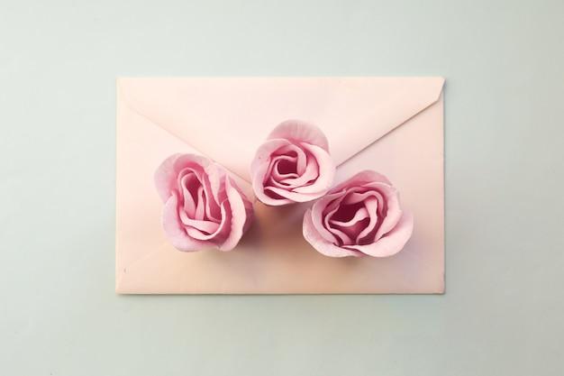 白い封筒、青い背景に3つのピンクのバラの花。ミニマルフラットレイ Premium写真
