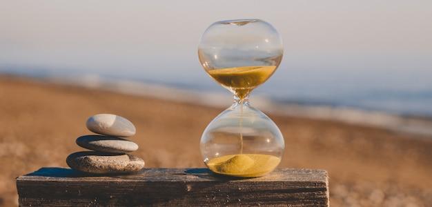 ピラミッドの形で3つの石で木の板に砂時計、海を背景に金色の砂のビーチでモダンな砂時計 Premium写真