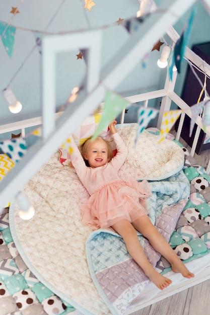 Счастливая 3-летняя девочка в розовом платье лежала на уютной кровати вниз. вид сверху. вид сверху Premium Фотографии