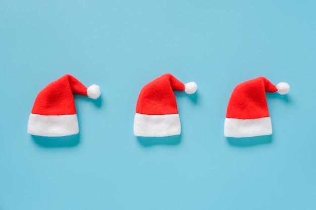 青色の背景に3つの赤いサンタクロースの帽子 Premium写真