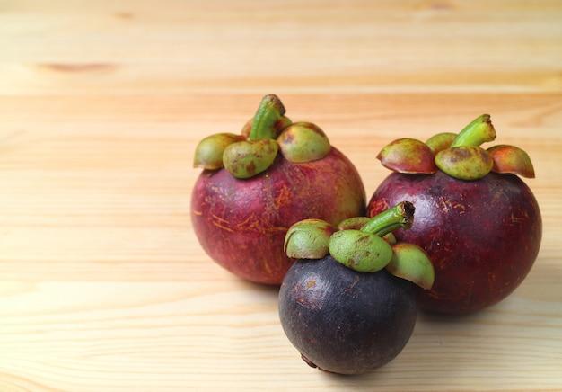 木製のテーブルに3つの異なるサイズと色熟した紫色のマンゴスチン果物 Premium写真