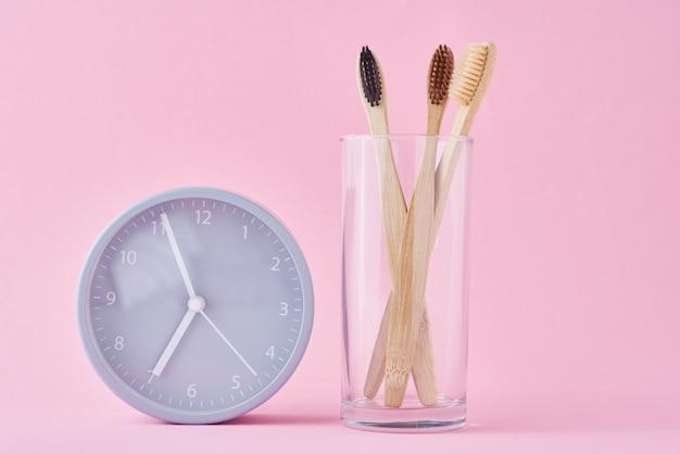 ガラスと目覚まし時計の3つの木製竹歯ブラシ。朝の衛生、歯科治療の概念 Premium写真