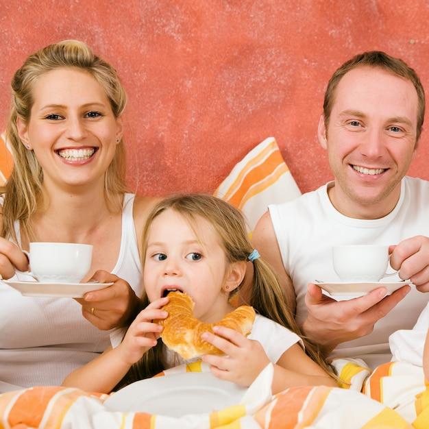 朝食を食べてベッドで3人家族 Premium写真