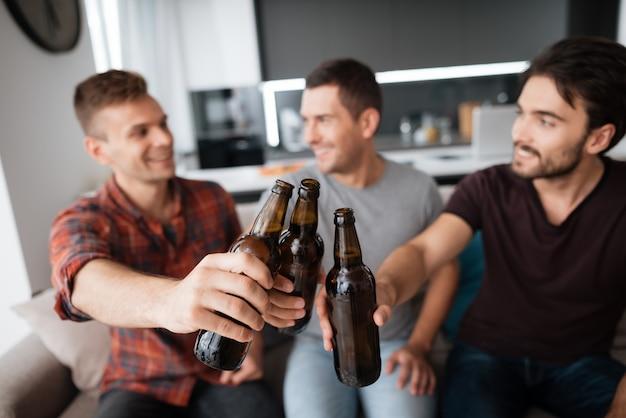 3人の男性がビールを飲みます。男はダークボトルを保持します。 Premium写真