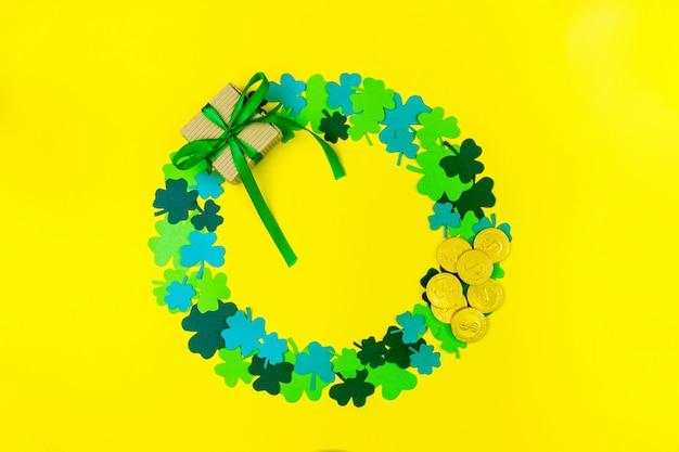 聖パトリックの日。緑の3つの花びらのクローバー、ギフトボックス、背景に横たわっている金貨の円形 Premium写真