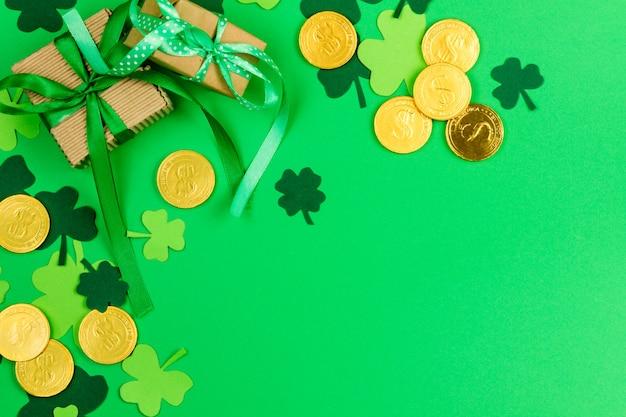 聖パトリックの日。緑の3つの花びらのクローバーと緑の背景の金レプラコーンコイン Premium写真