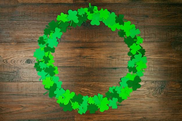 聖パトリックの日。木製の背景に緑の3つの花びらのクローバーの円形 Premium写真
