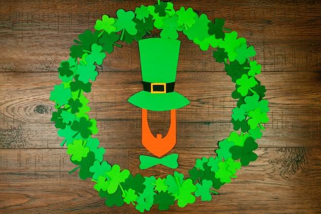 聖パトリックの日。緑の3つの花びらのクローバーの円形の木製テーブルの上に横たわる帽子のレプラコーンのシルエット Premium写真