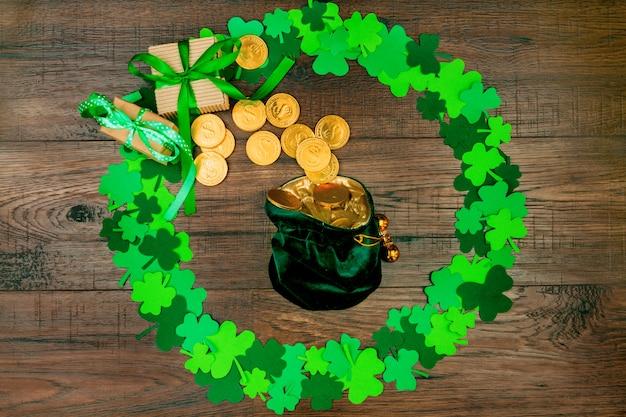 聖パトリックの日。緑の3つの花びらのクローバーの円形の木製テーブルの上に横たわる金貨とレプラコーンの小さな袋 Premium写真