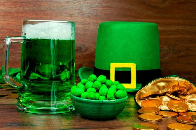 聖パトリックの日。ビールの緑のガラスパイント、緑のスナッククッキーお菓子、レプラコーンの緑の帽子、緑の3つの花びらのクローバー、木製のテーブルの上の金貨 Premium写真