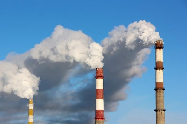 青い空を背景に3つの工場の煙突から煙や蒸気の密な雲。生態学、環境汚染の概念。 Premium写真