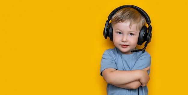黒のヘッドフォンで遊んでで3歳のハンサムなかわいい金髪の少年 Premium写真