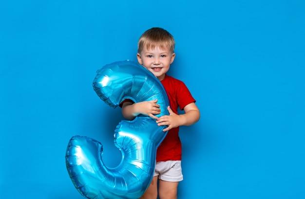 ホイルコート球バルーンブルー色を保持している小さなかわいい金髪の少年。 3歳お誕生日おめでとう Premium写真