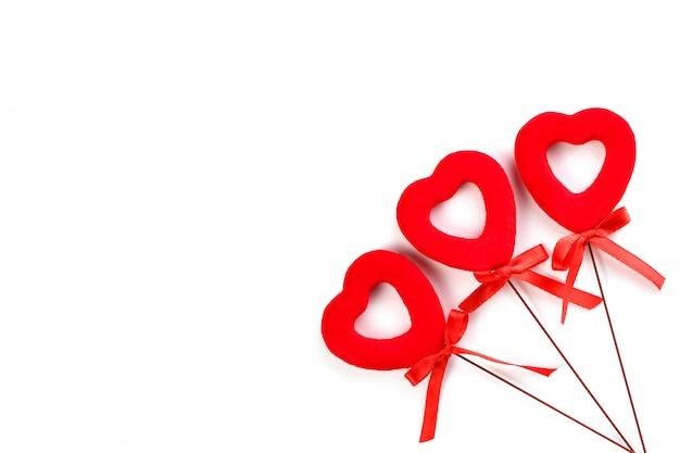 白い表面に弓と3つの赤いハート Premium写真