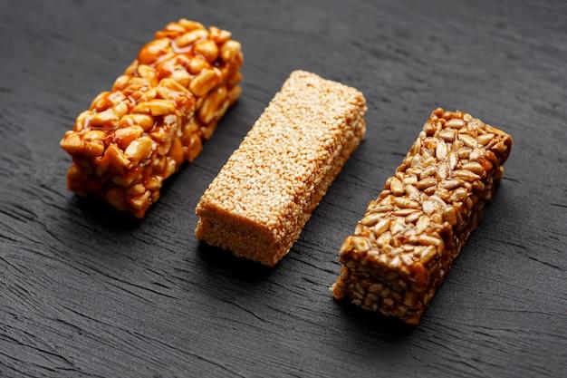 暗い石のテーブルのまな板の上のピーナッツ、ゴマ、ヒマワリの種を持つ穀物グラノーラバー。上からの眺め。 3つの盛り合わせバー Premium写真