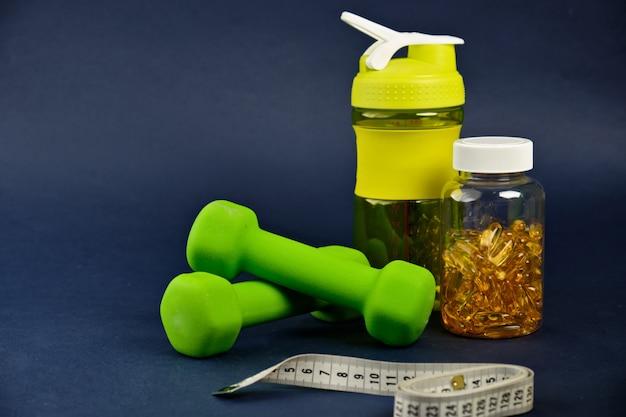 プラスチックシェーカー、緑のダンベル、オメガ3缶 Premium写真
