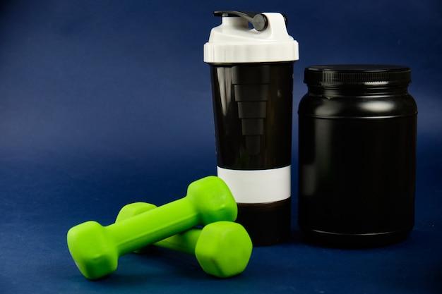 黒い瓶に入ったタンパク質、プラスチックシェーカー、緑色のダンベル、オメガ3缶 Premium写真