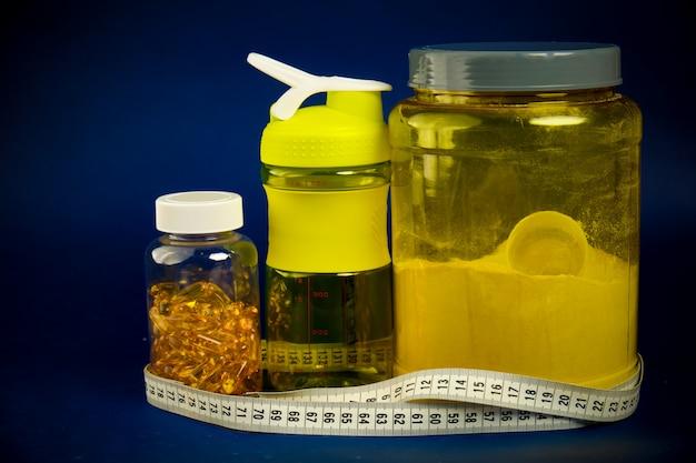 黄色い瓶、プラスチックシェーカー、緑のダンベル、オメガ3瓶に入ったタンパク質 Premium写真