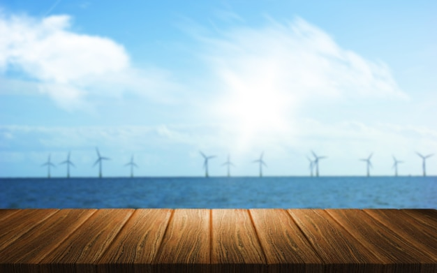 3d background of a wooden table looking out to a wind farm in the sea Free Photo